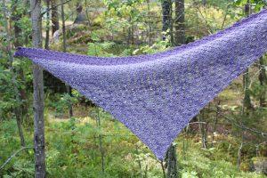 Corner to corner crochet shawl hanging in forest